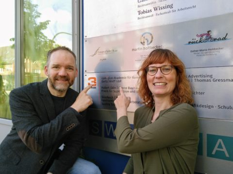 Christian Gertz und Constanze Wolff vor ihrem neuen Schild der complus Akademie für Kommunikation.