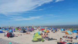 Menschen in Strandkörben am Nordsee-Strand in Schillig.