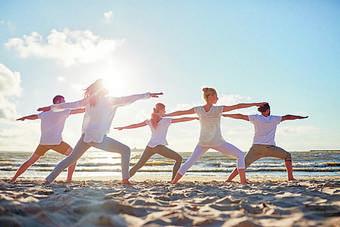 Eine yogapraktizierende Gruppe Menschen an der Nordsee