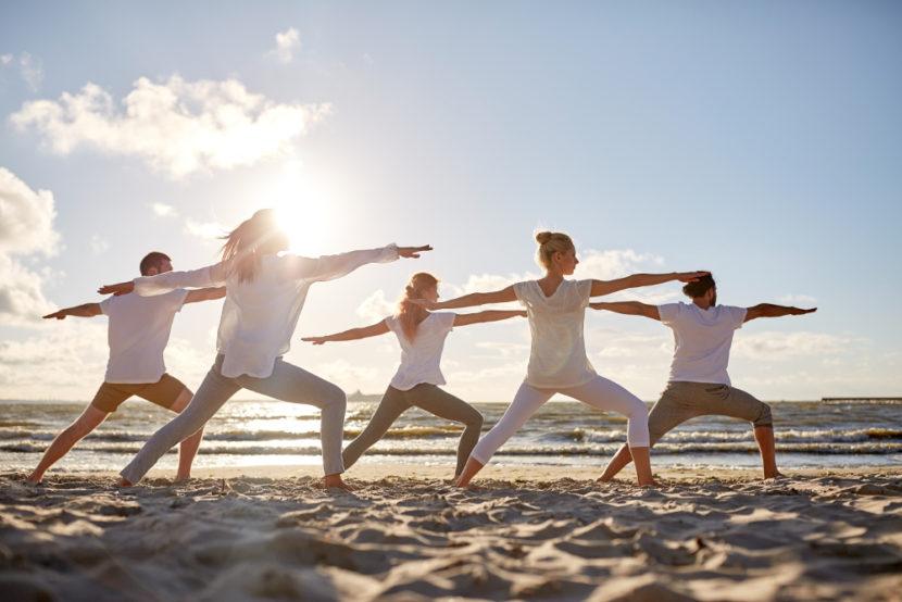Menschen praktizieren Yoga an der Nordsee am Strand.