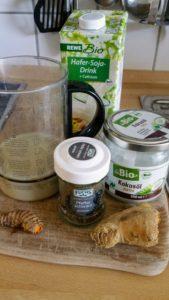 Zutaten für Goldene Milch Ingwer, Kurkuma, Pfeffer, Kokosöl, Soja-Milch auf Anrichte